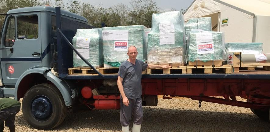 Prof Ian Goodfellow standing in front of a lorry full of supplies